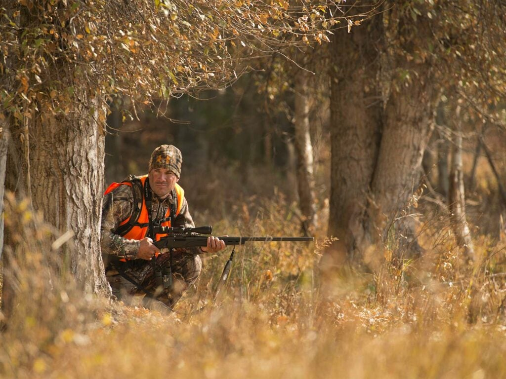 A hunter in full camo kneels behind a tree and grips a rifle in both hands.