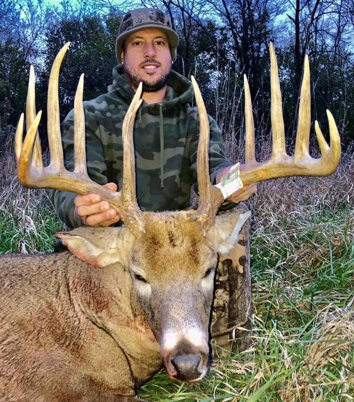 A hunter kneels behind a large deer.