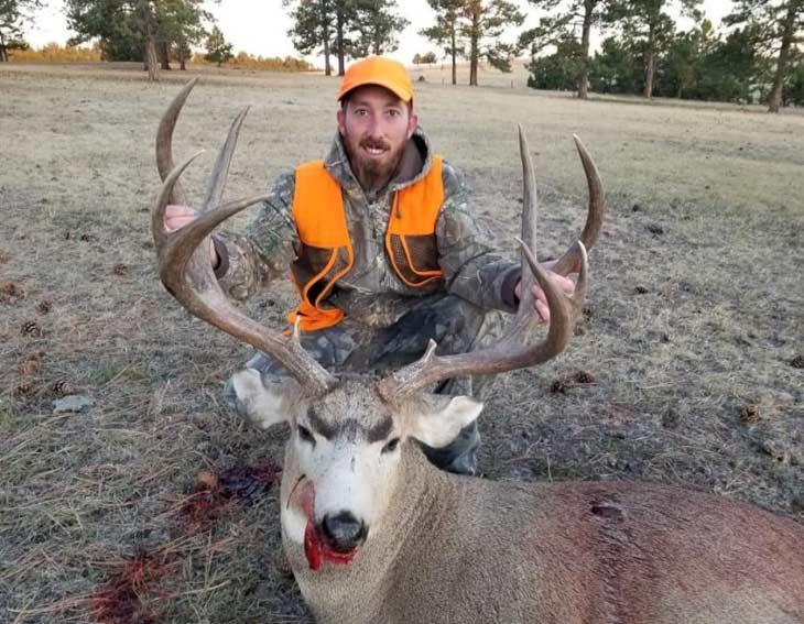A hunter kneels behind a large buck.
