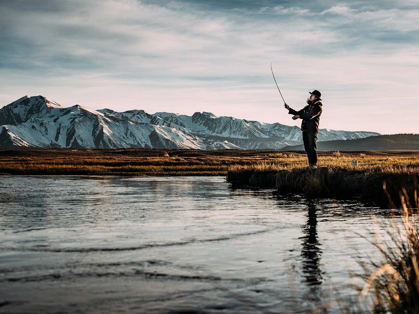 An angler fishing a river side with snowy mountains in the distance.