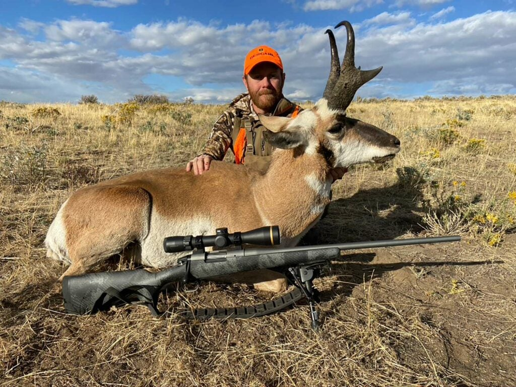A hunter kneels behind a large antelope in an open field.