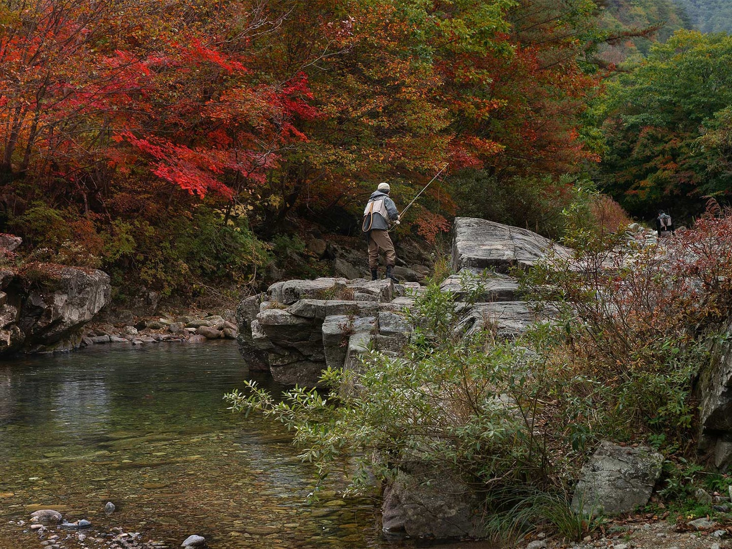 An angler stands on a rocky outcrop over a stream.