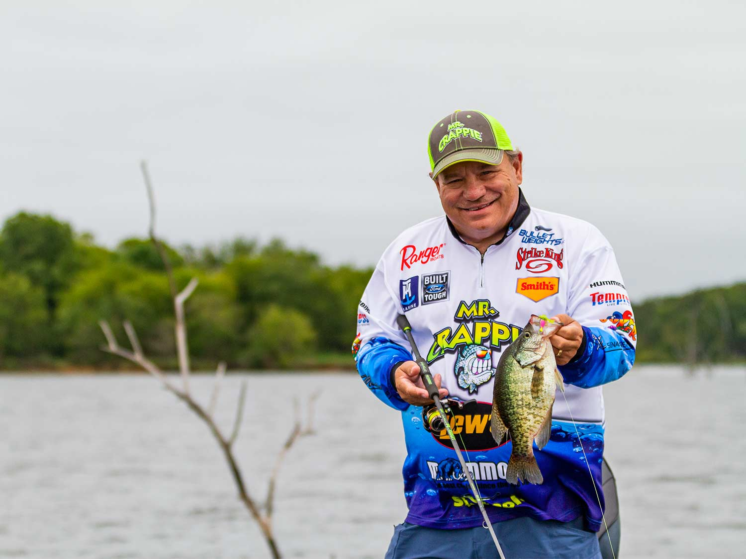An angler holds up a crappie caugh on a lews rod.