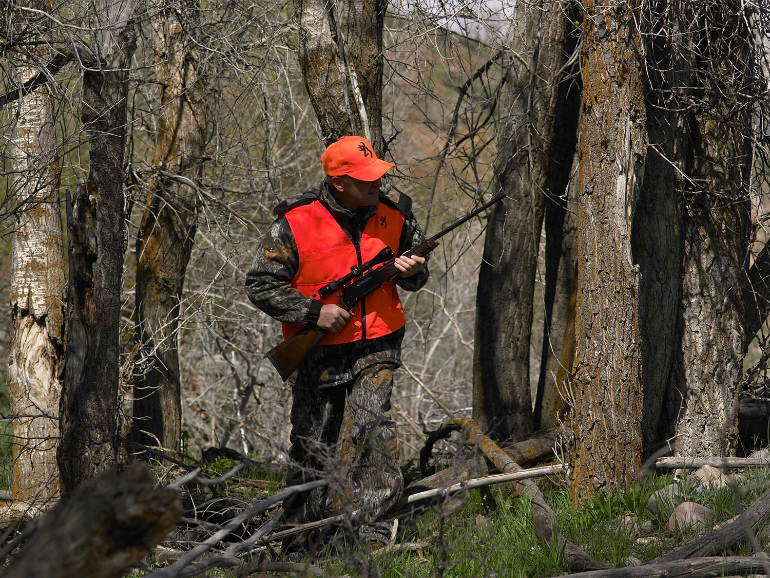 A hunter in camo and orange holding a rifle in the woods.