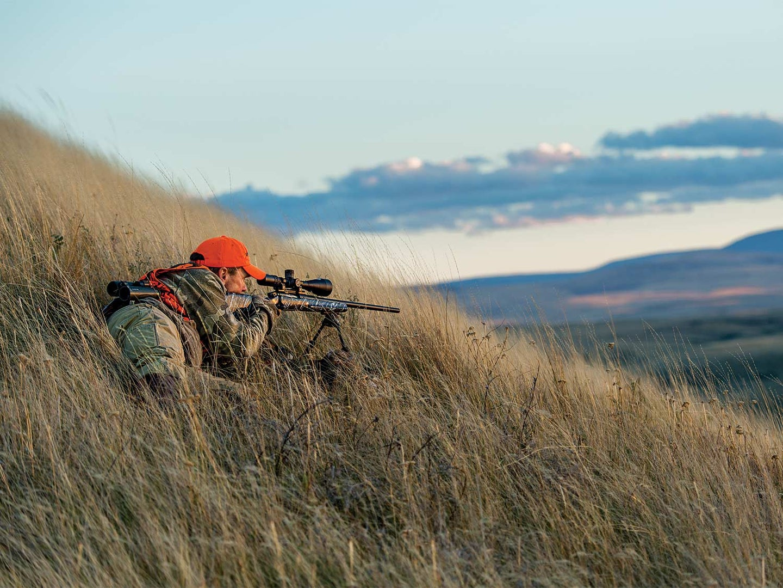 A hunter aims a rifle on the hillside.