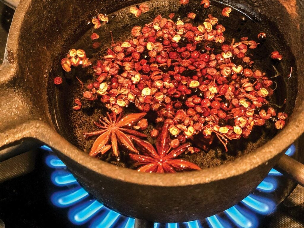 A small pot of chili, oil and star anise on a small cooking burner.
