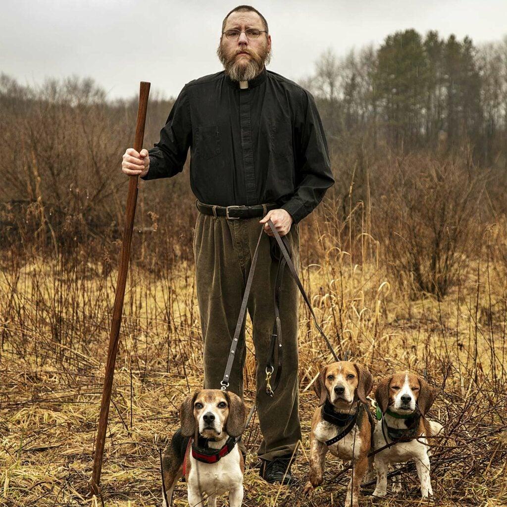 A hunter holds three beagles on a leash.
