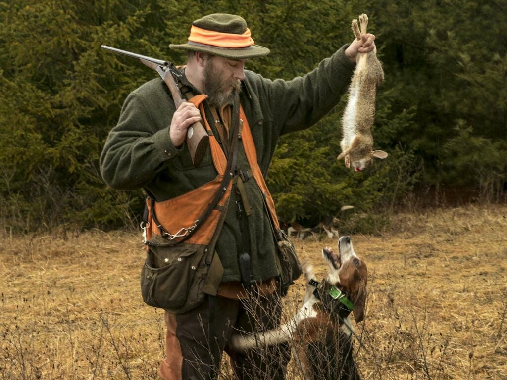 A hunter holding up a rabbit away from a beagle.