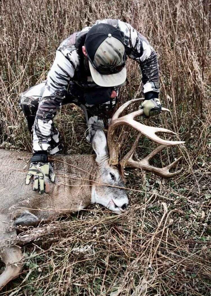 Brett Schmit recovers his buck after a perfect shot.