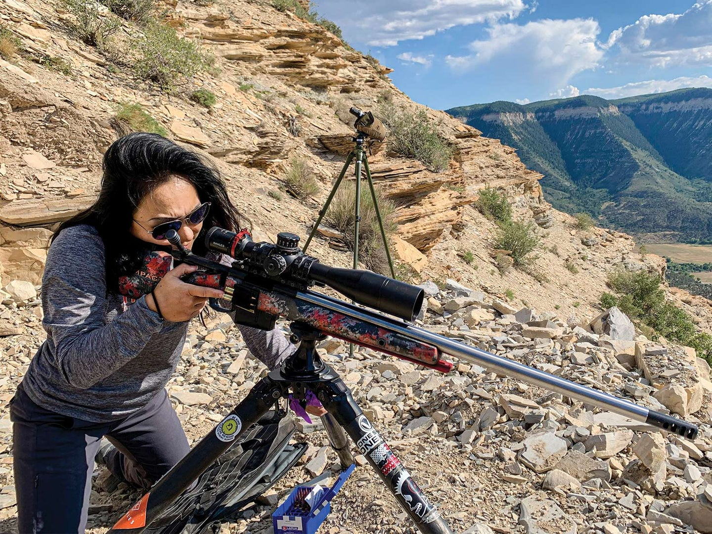 A woman wearing shooting protective gear, aims a rifle that is scoped and propped up on shooting sticks.
