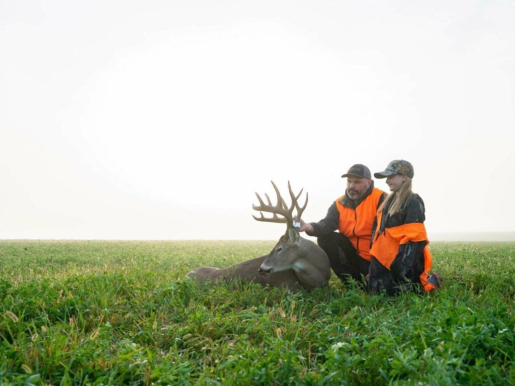 A young girl and her stepfather admire the buck taken in a large open field.