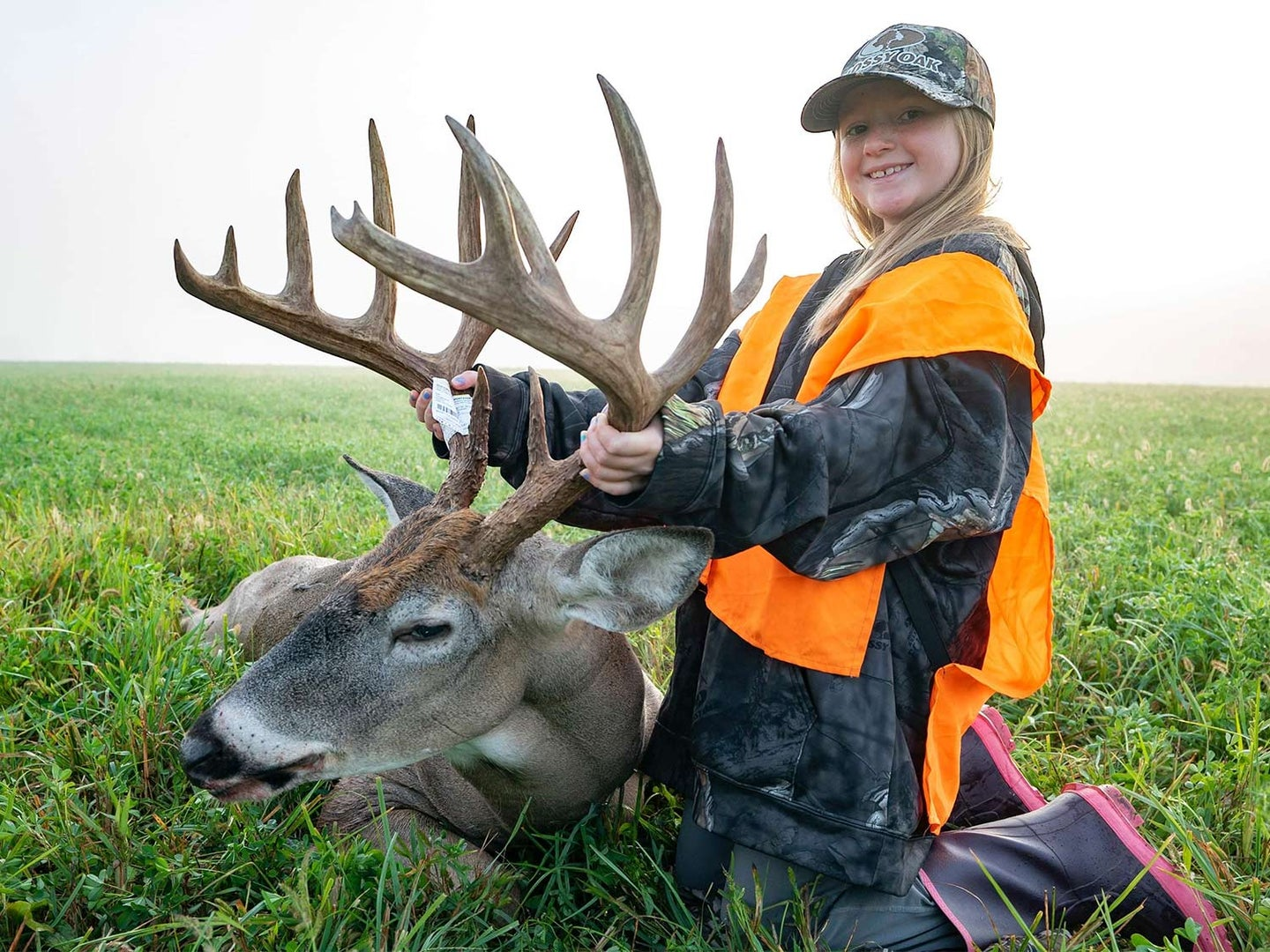 A young girl holds up a deer head by the antlers.