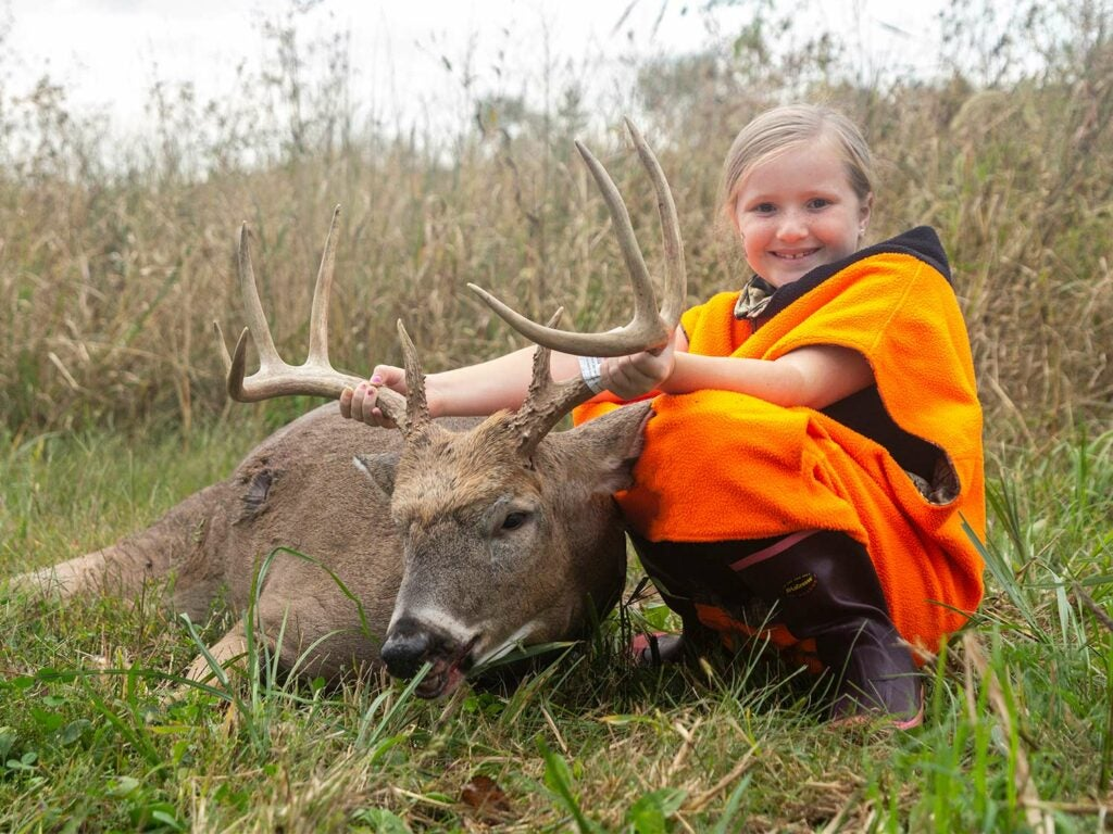 A young girl holds up the antlers of a deers head.