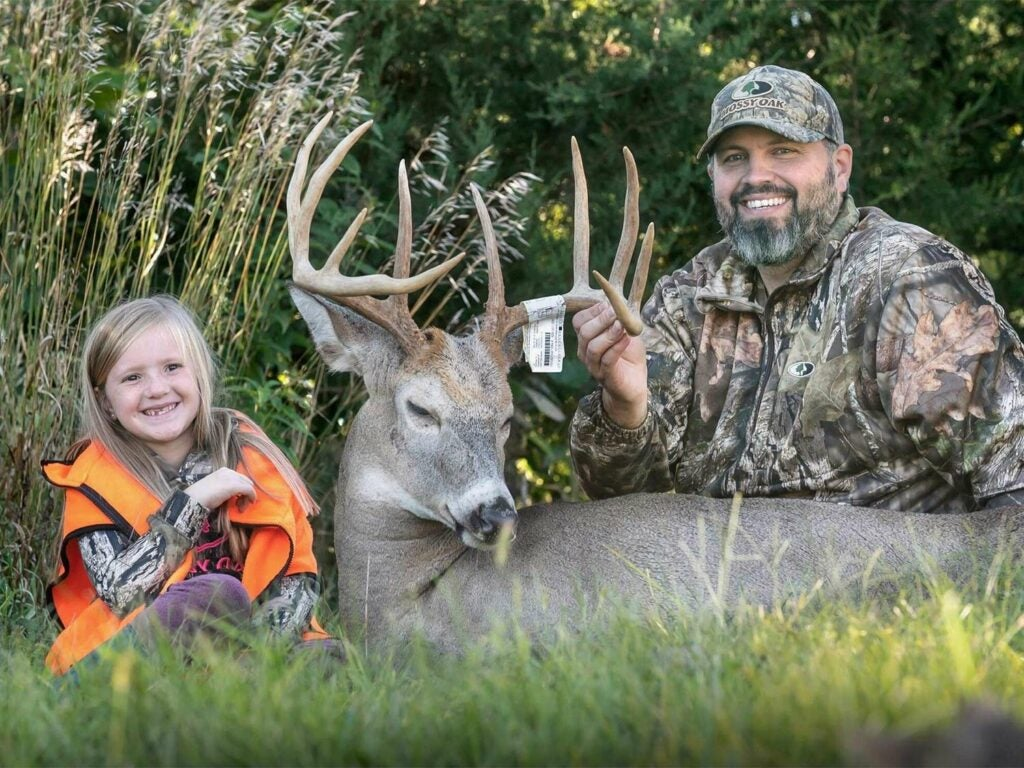 A young girl and stepfather kneel behind a large buck.
