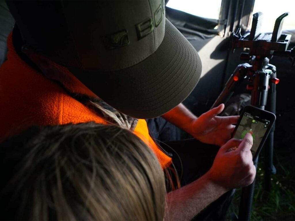 A stepfather shows daughter how to use an app for locating their hunting spot.