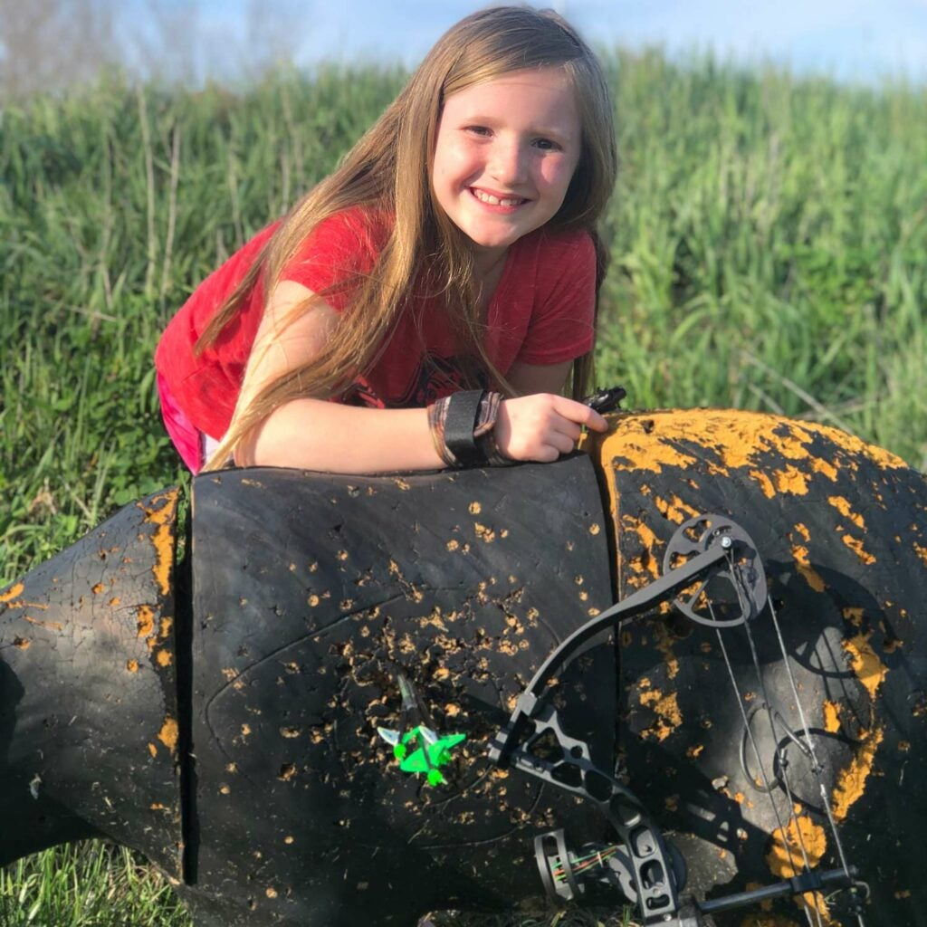 A young girl shows off a group of arrows tightly grouped in the target of a deer decoy.