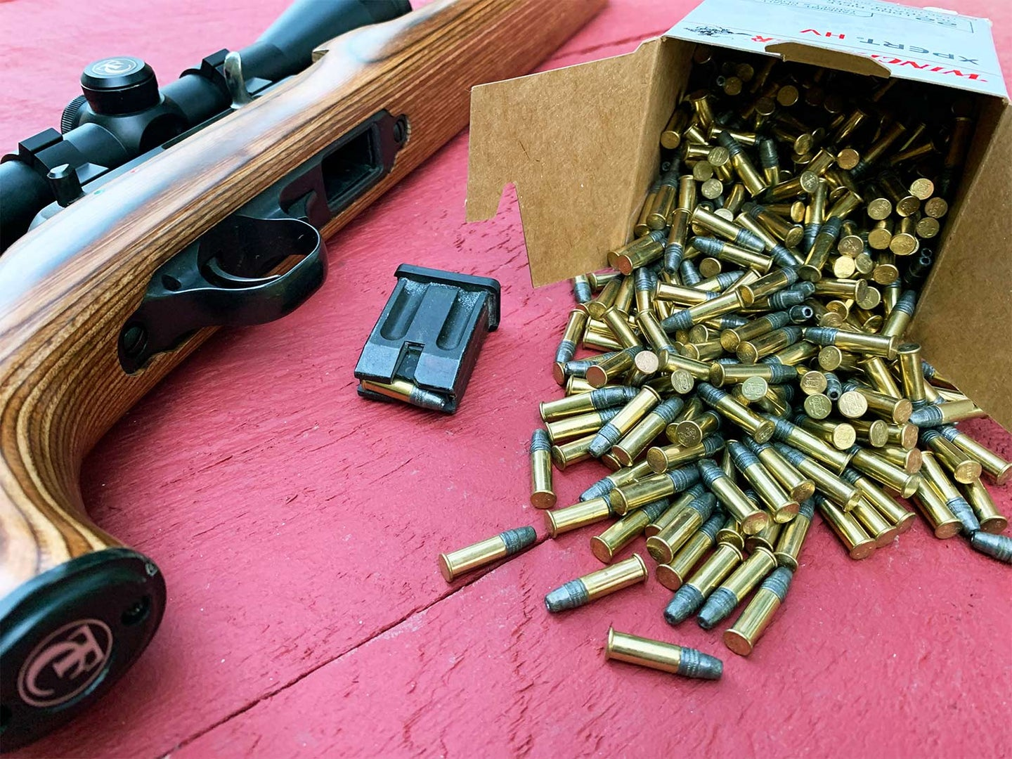 A rifle on a table next to a box of rifle ammunition spilling out onto the table.