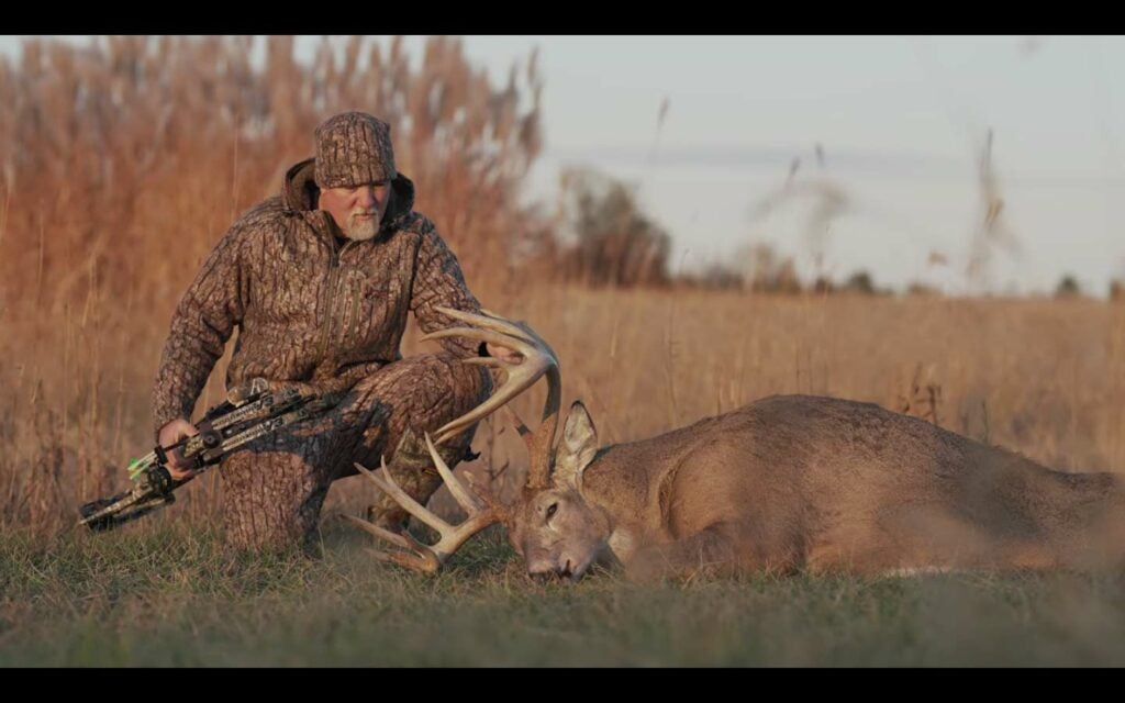 A hunter sits next to a dropped whitetail buck in a large open field.