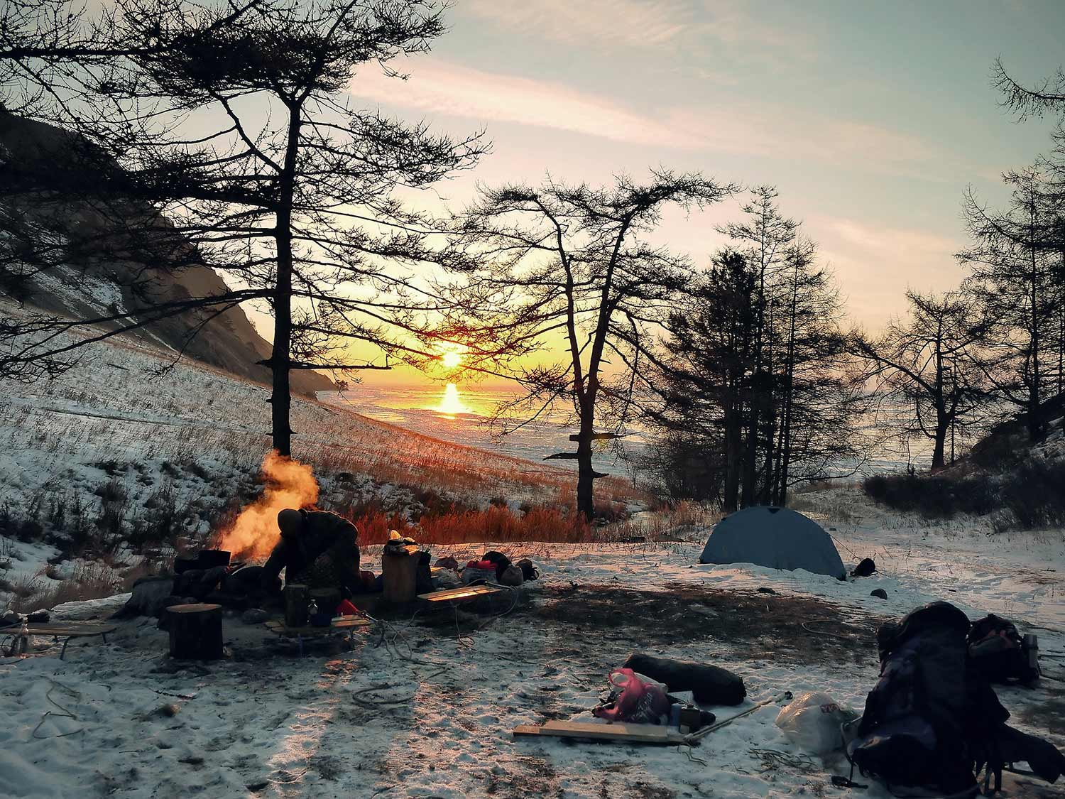 A wintry landscape with a small campsite and burning fire.