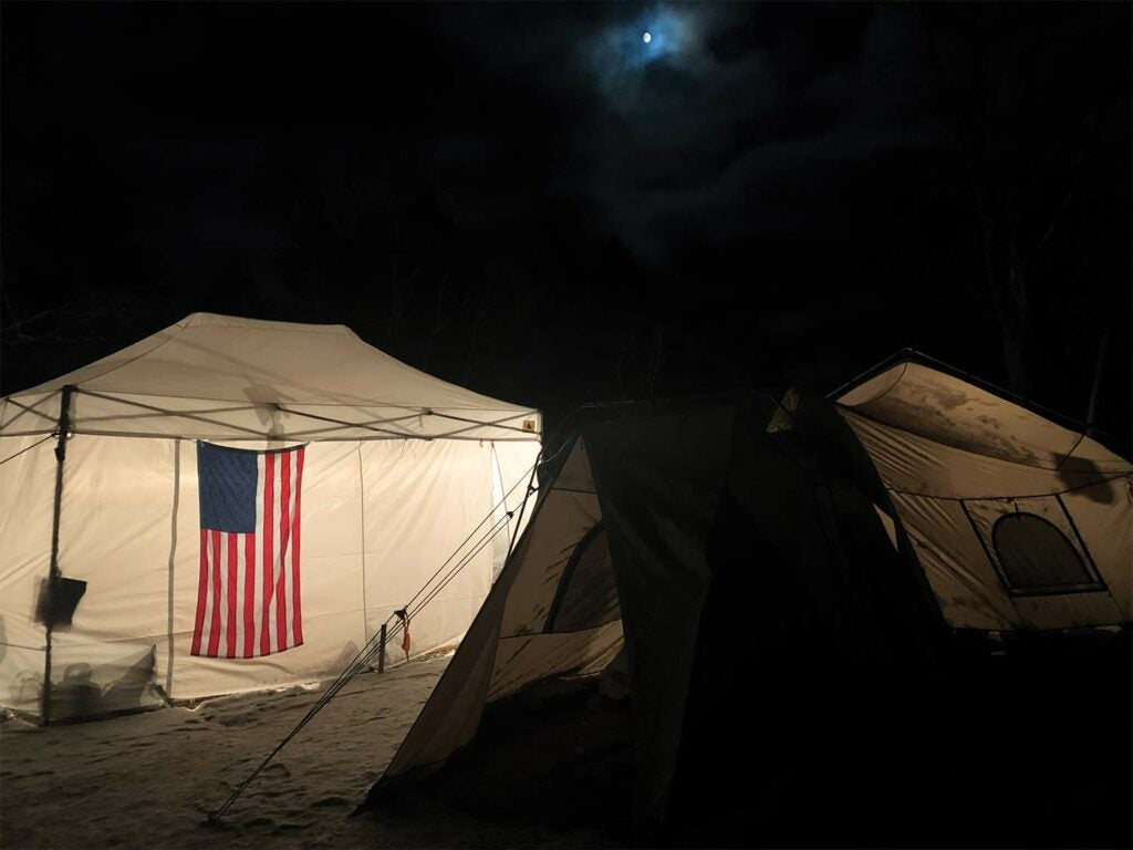 An American flag hanging on the outside of a white camping tent at night.