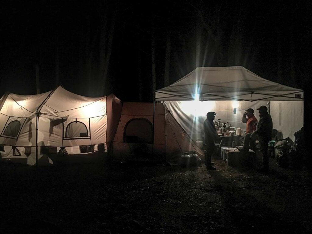 Groups of hunters stand outside of a lit camping tent at night.