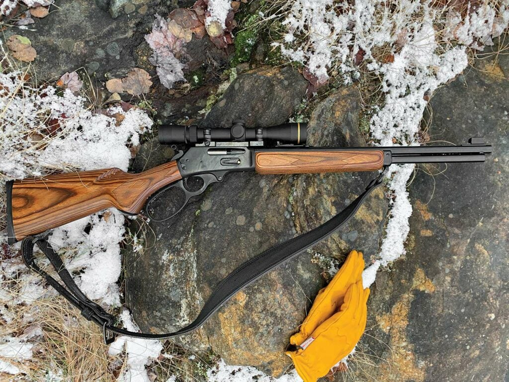 A lever-action rifle resting on a snow-covered rock.