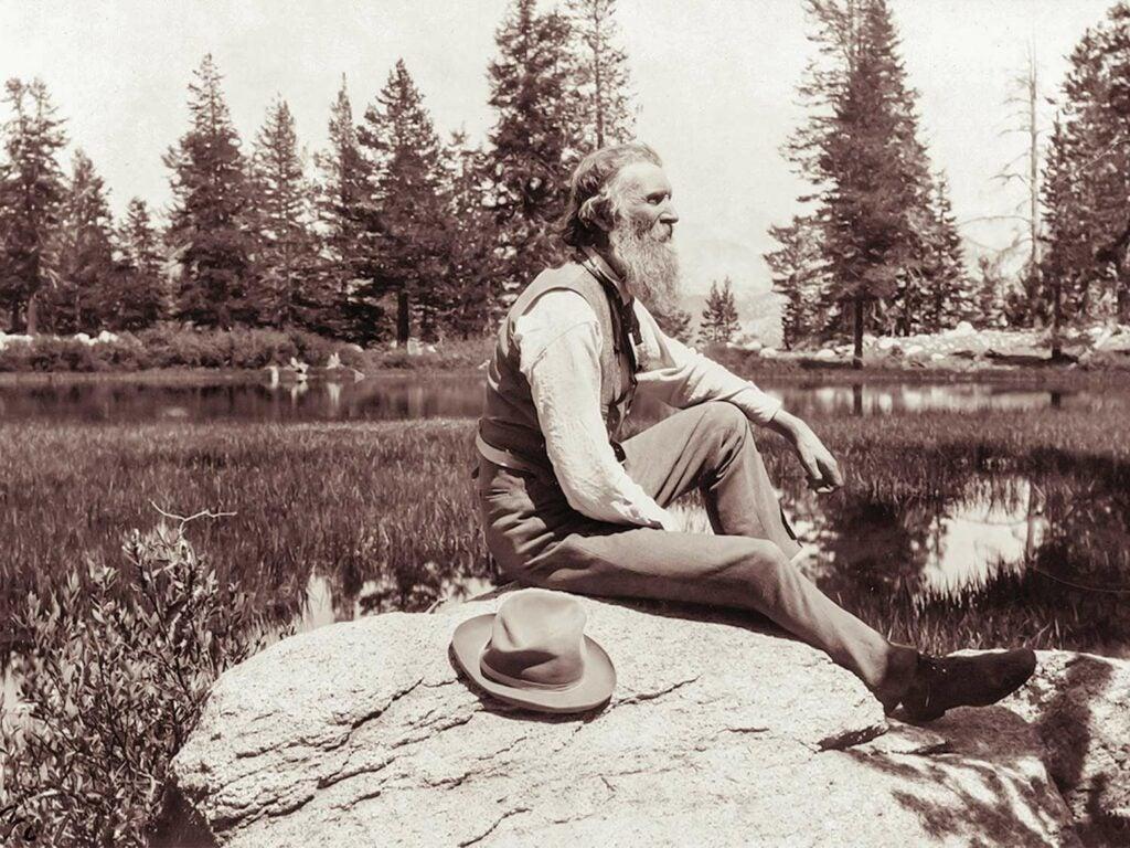 John Muir sitting on a rock.
