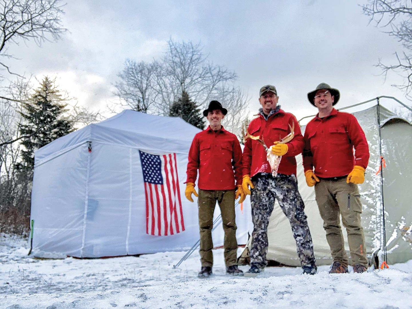 Three men in red stand in the snow holding a deer head skull.