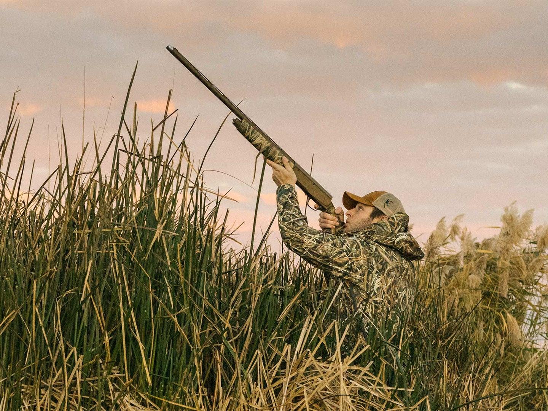A hunter aims a shotgun in the air.