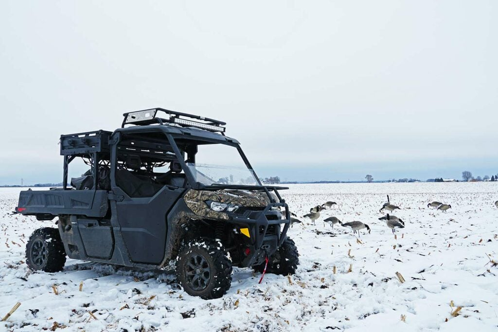 A Can-Am Defender Pro UTV in a field of snow next to goose decoys.