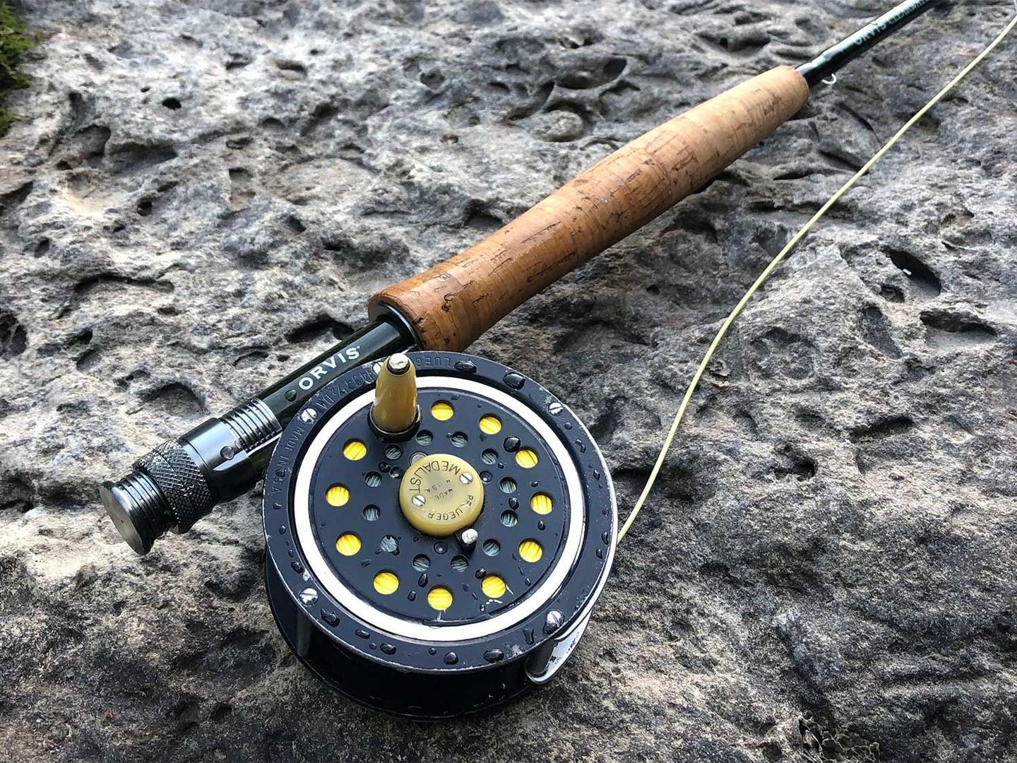 An Orvis reel and Pflueger fly reel on a stone by the water.