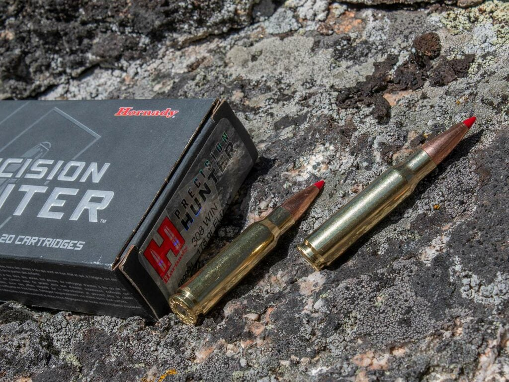 A box of Hornady Precision Hunter and ammunition on a rock.