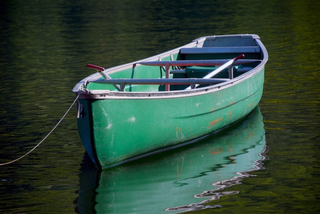 a single canoe tethered to a dock floats on the water.