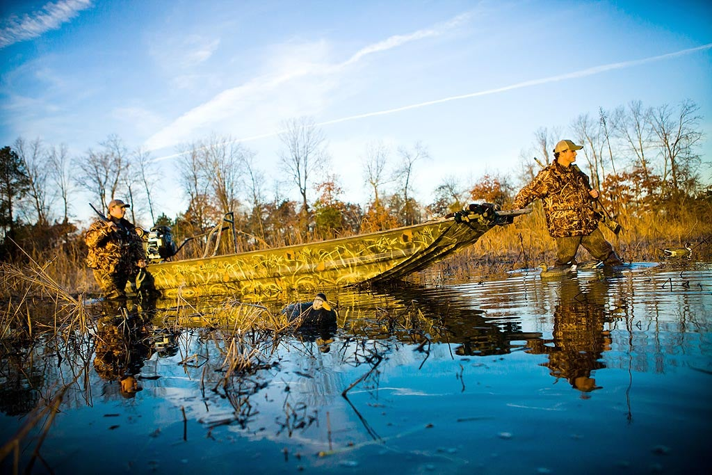 An aluminum war eagle duck boat is pulled through the water by two hunters.