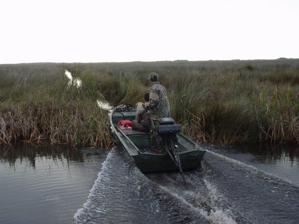 A hunter drives a jon boat with a long-tail engine.