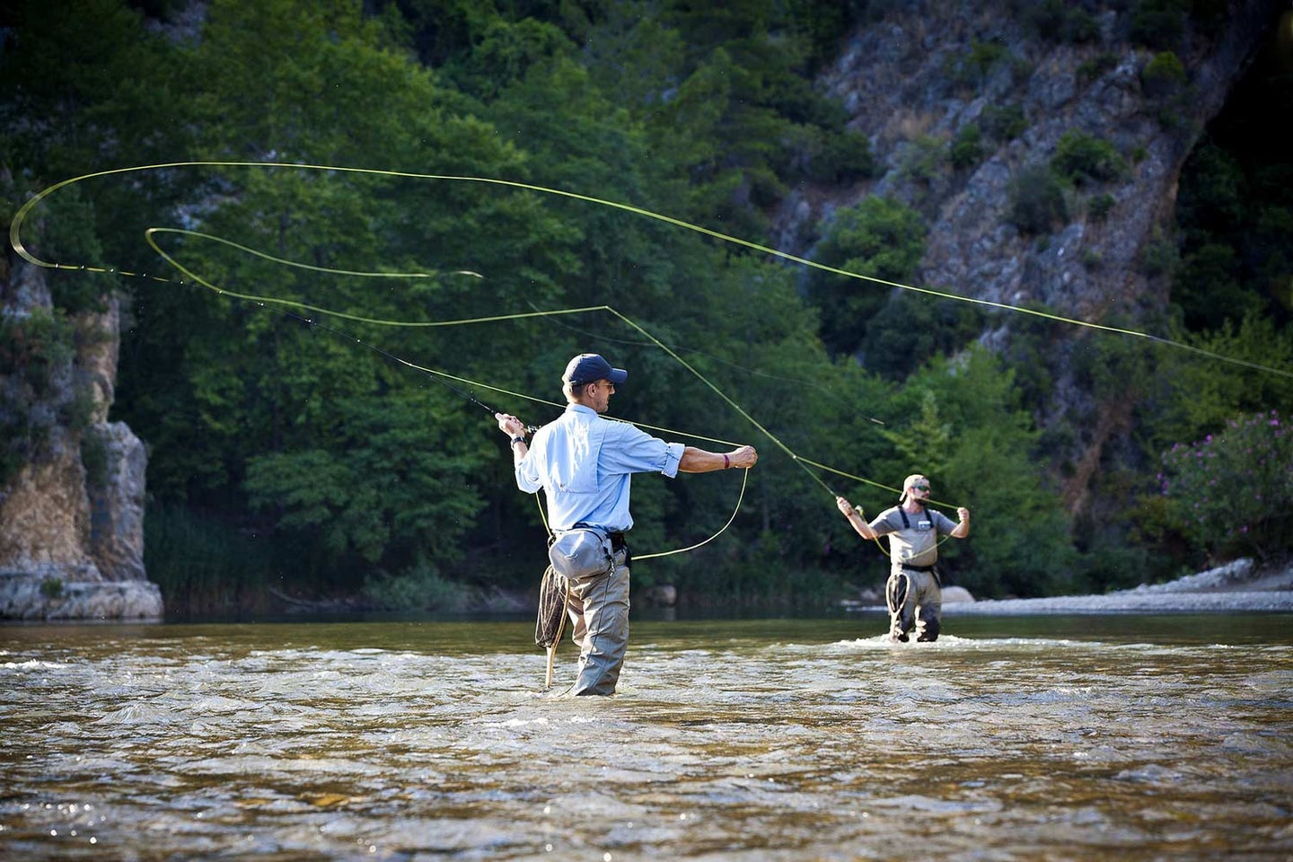Two anglers cast their reels into a flowing stream.