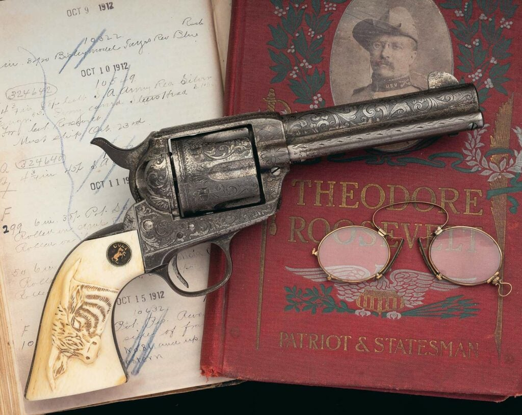 A colt single action army revolver on a book of Teddy Roosevelt.