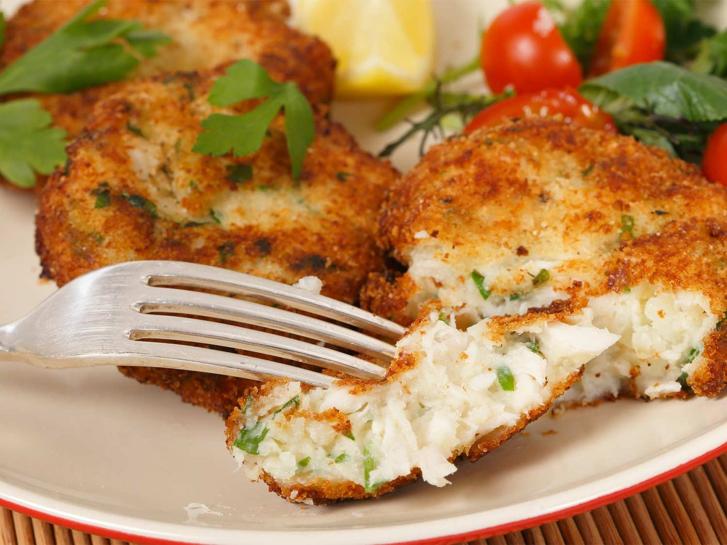 A fork cuts into a fish cake.