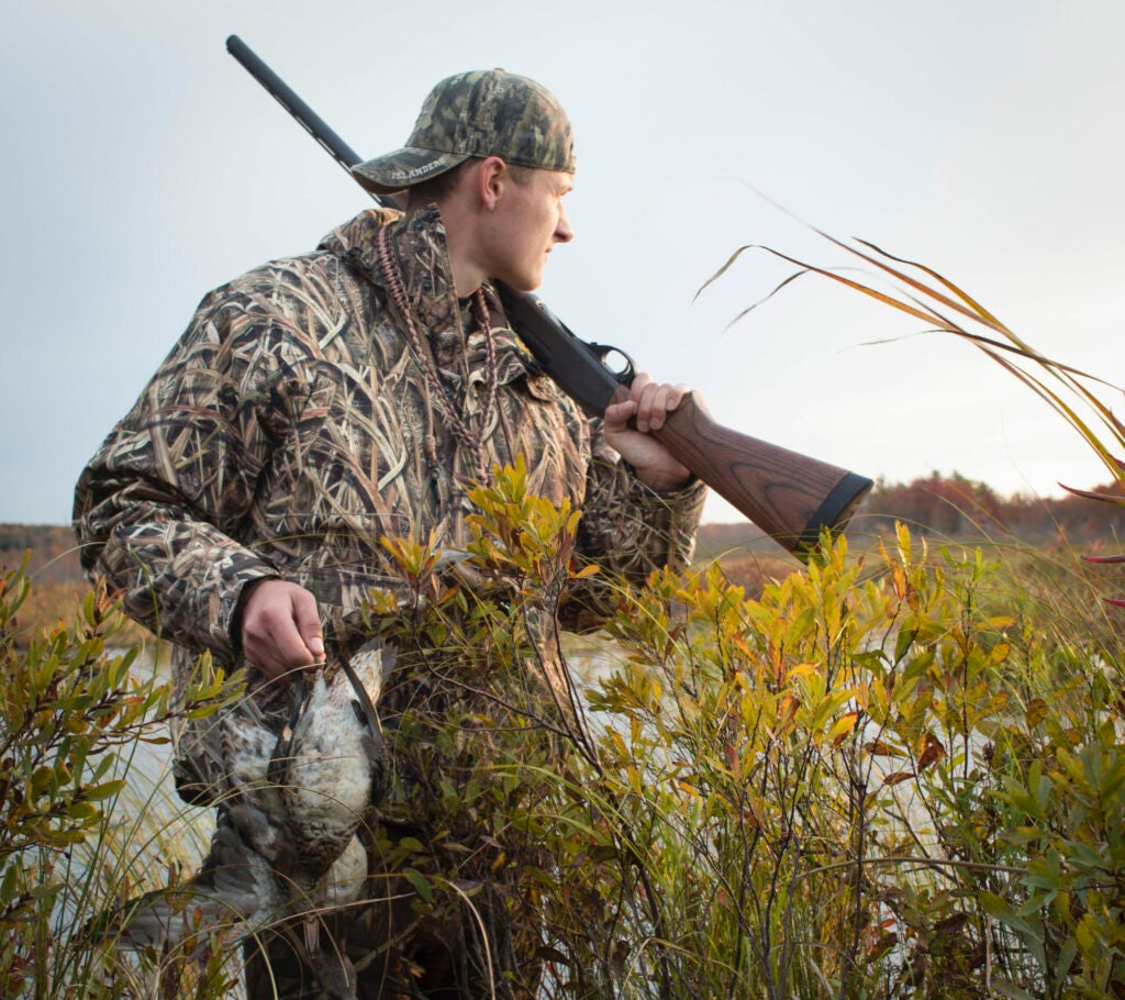 A hunter holds a rifle in one hand and a duck in the other.