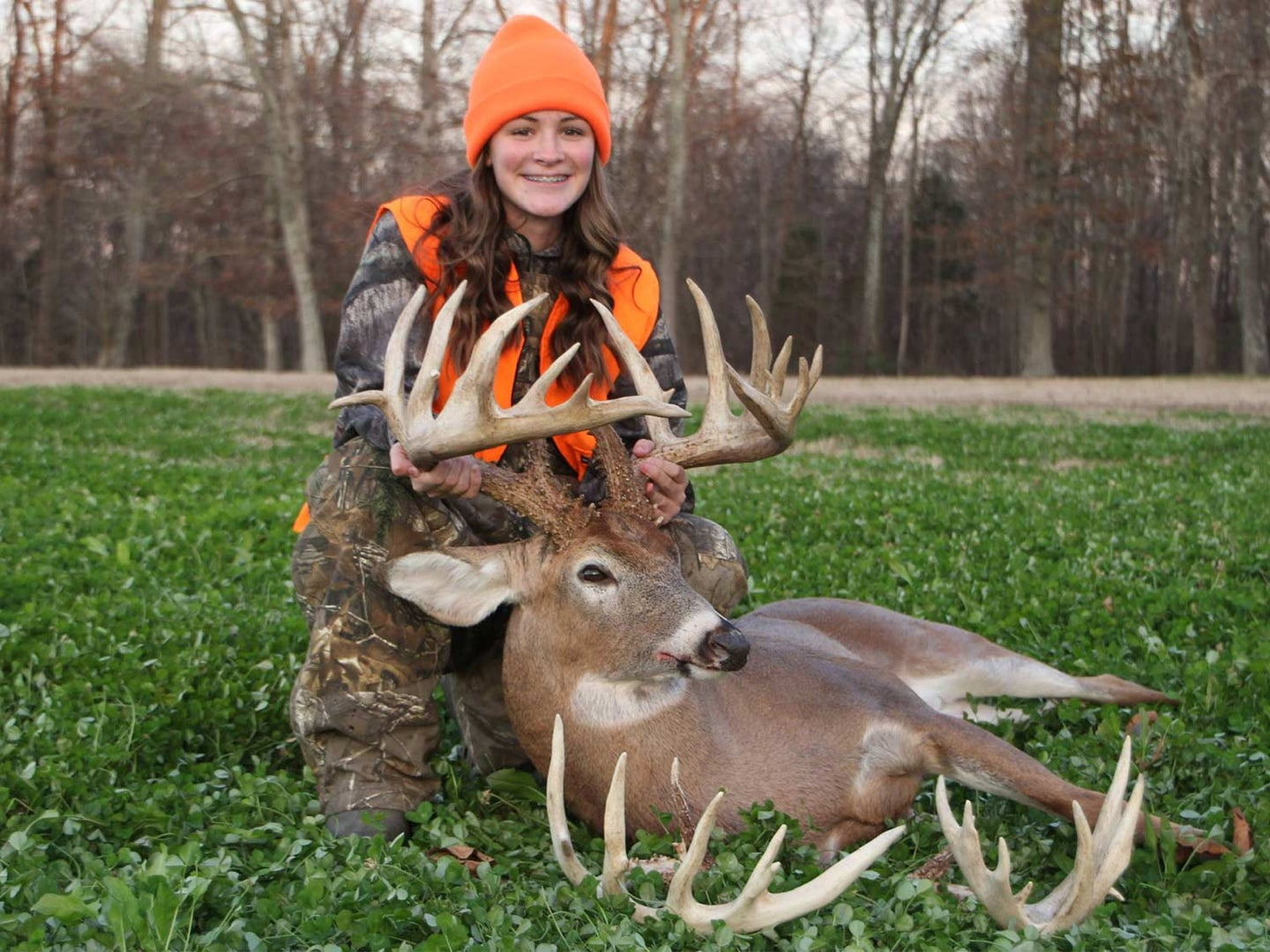 A young girl poses with a whitetail deer and holds its head by its antlers.