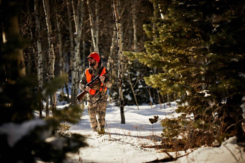 Hunter wearing orange vest, walking in the snow