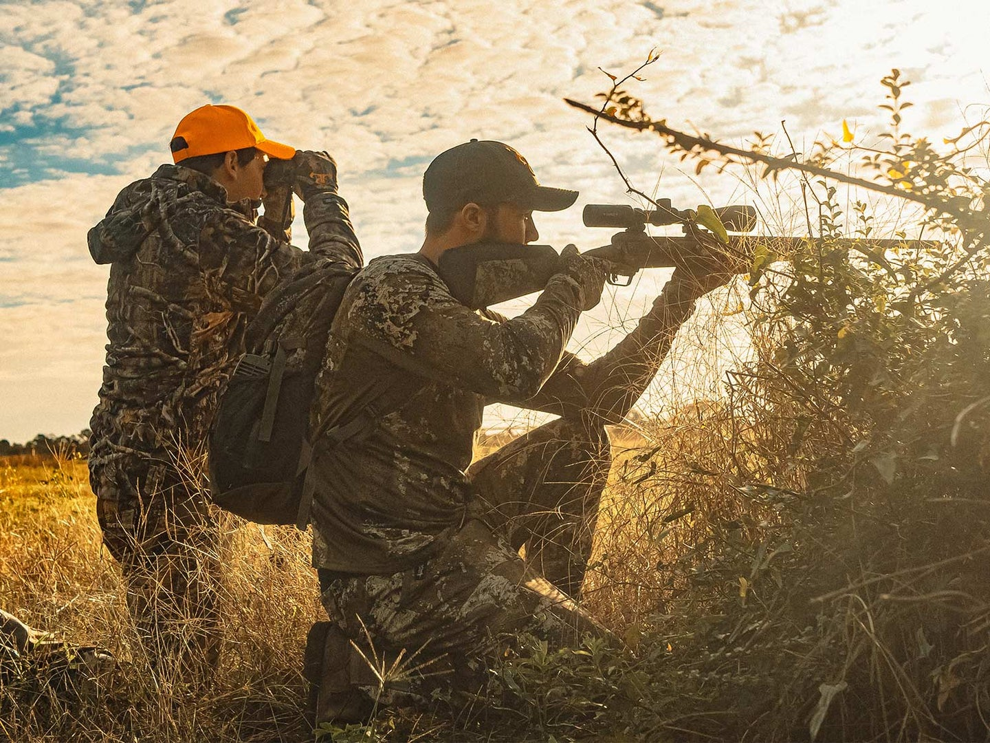 Two hunters kneel, scout, and aim their rifle in an open field.
