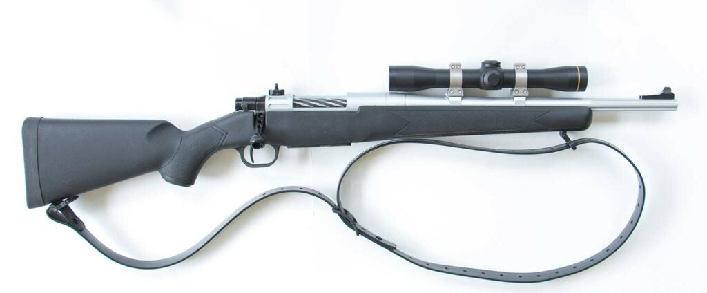 A custom scout rifle built from a Mossberg rifle on a white background.