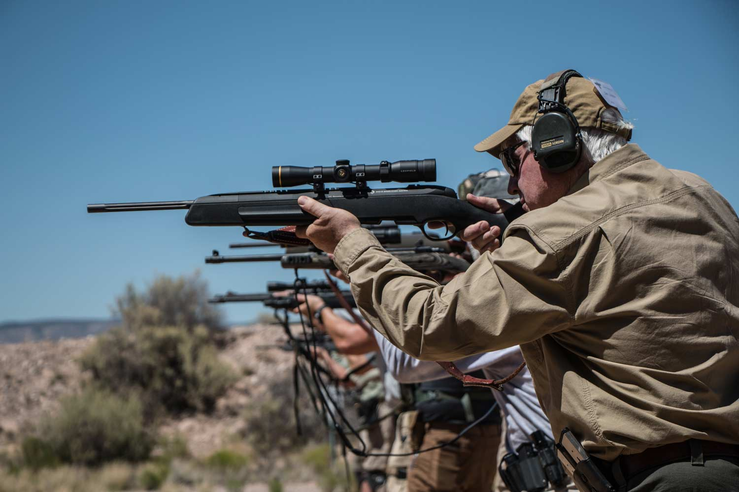 A line of men aim scout rifles at a shooting range.