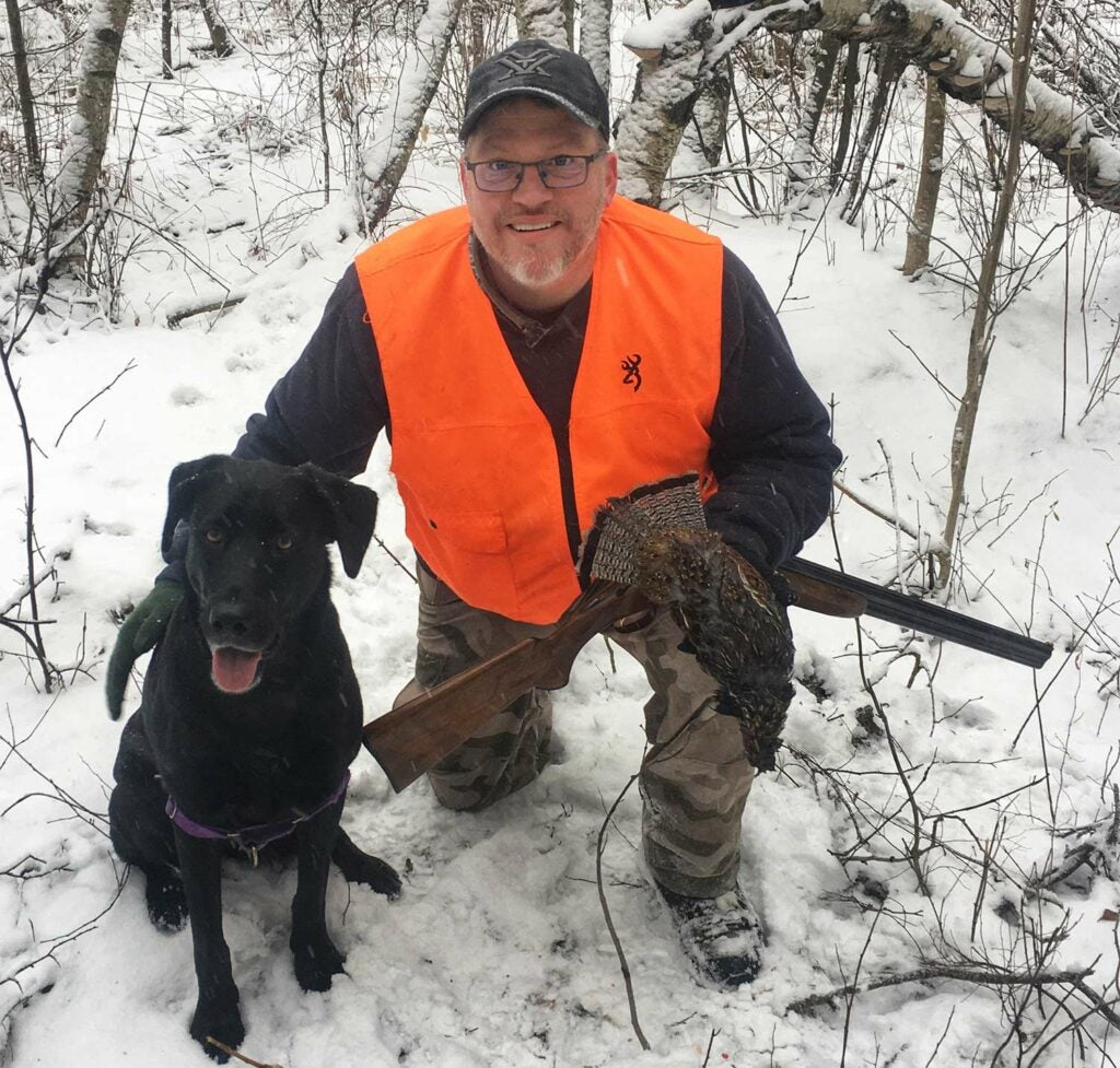 A hunter kneels in the snow and pets his hunting dog while holding a ruffed grouse.