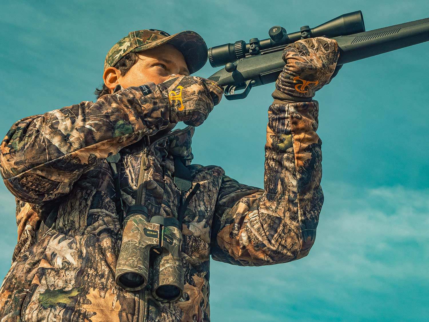 A hunter holds a rifle up to their shoulder.