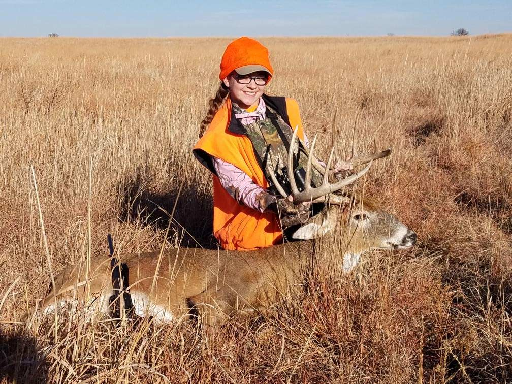 A young girl poses next to a whitetail buck.
