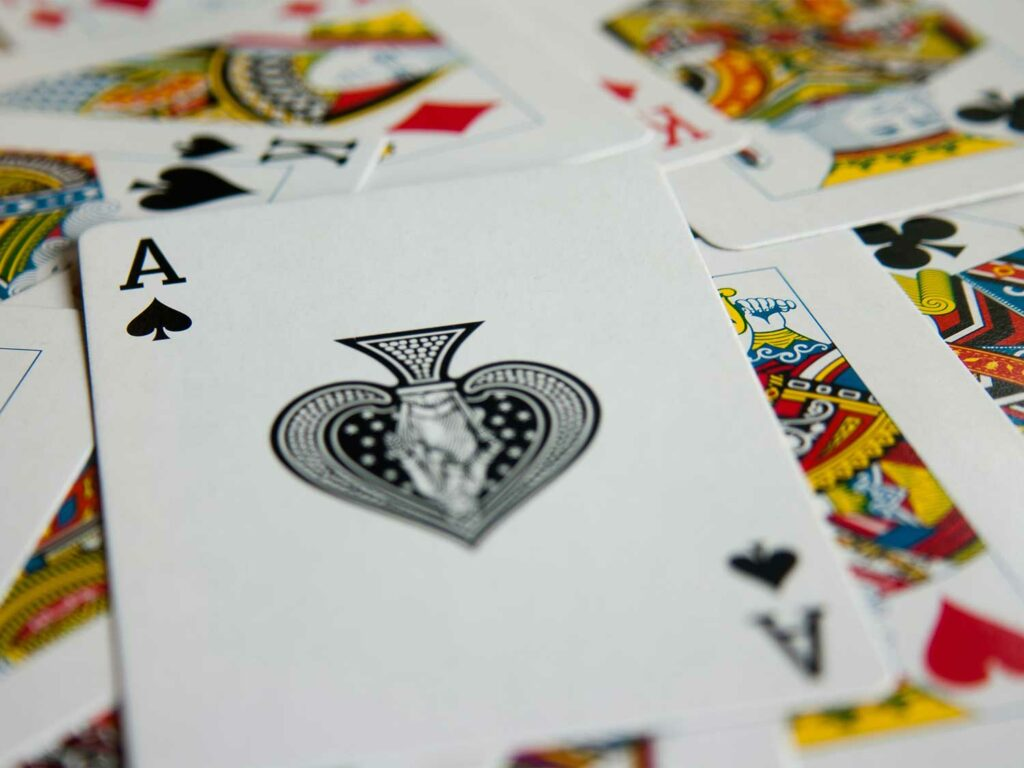 An Ace of Spades card on a pile of other playing cards.