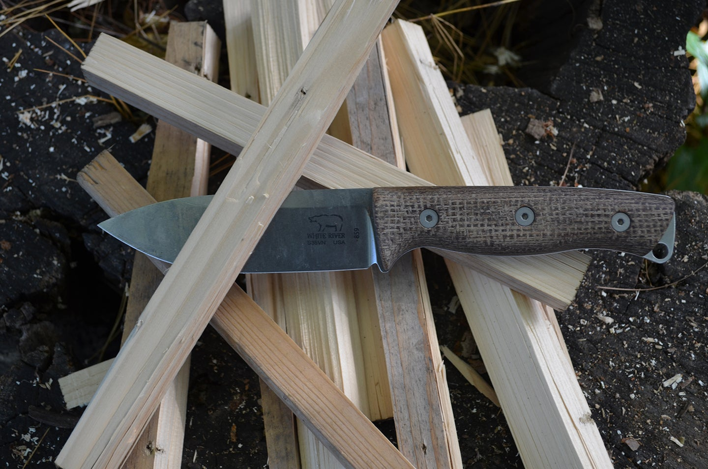 A bushcraft knife in a pile of wood pieces.