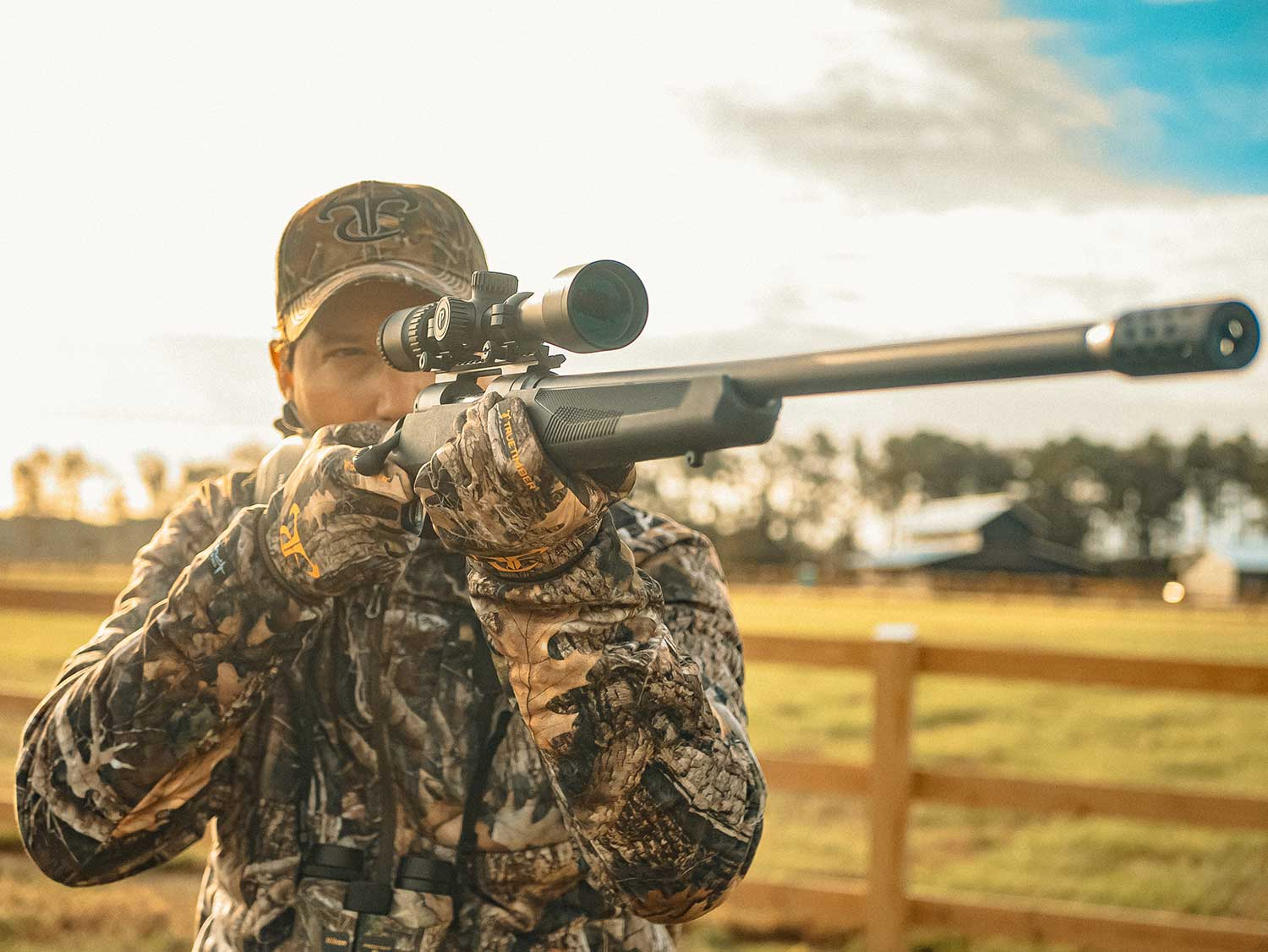 A deer hunter in full  camo aims a rifle in a field.